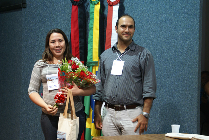 Congressista Maria das Dores de Souza Abreu recebendo premiacao das maos de Thiago Silva.